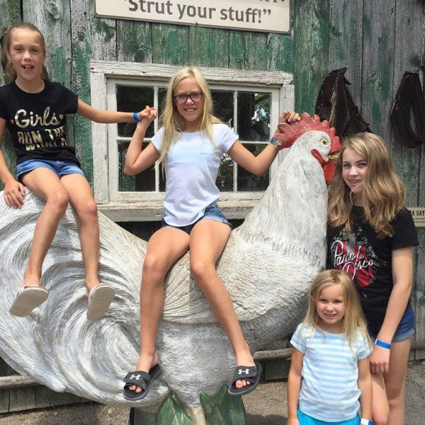 Children sitting on a large chicken statue