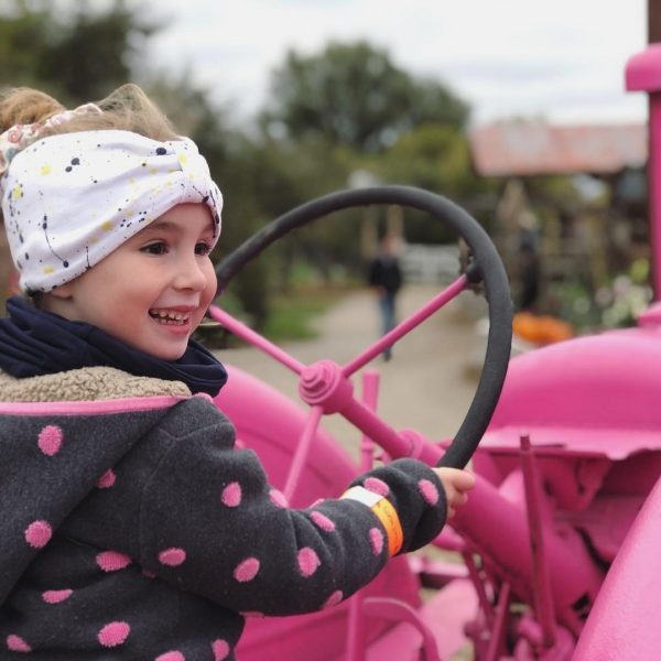 Girl sitting on pink tractor