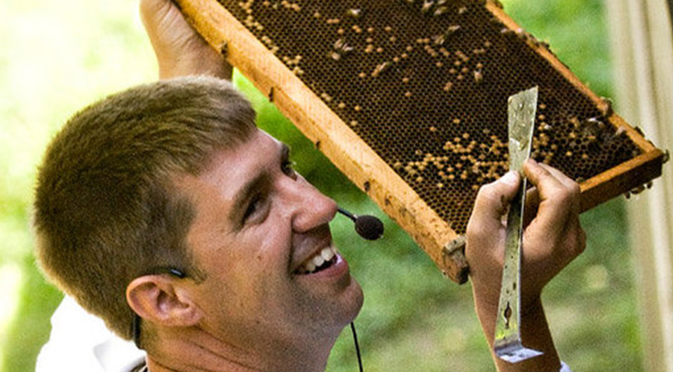A man showing the inside of a bee hive