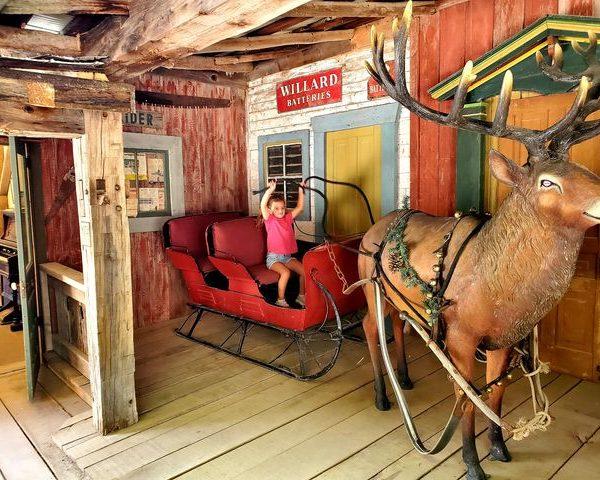 Child sitting on the sleigh behind Reindeer