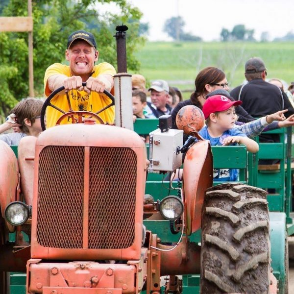 Worker Bee driving the tractor, with people on sitting on the wagons